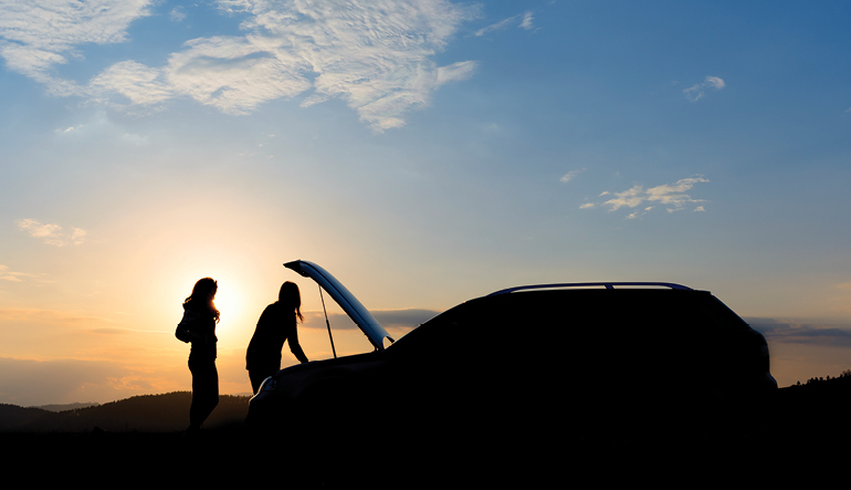 Two women working on car during sunrise.