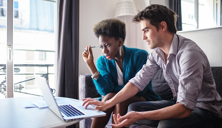 woman and man looking at finances on laptop