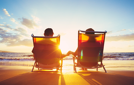 an older couple relaxing on the beach thanks to sdccu ira money market account