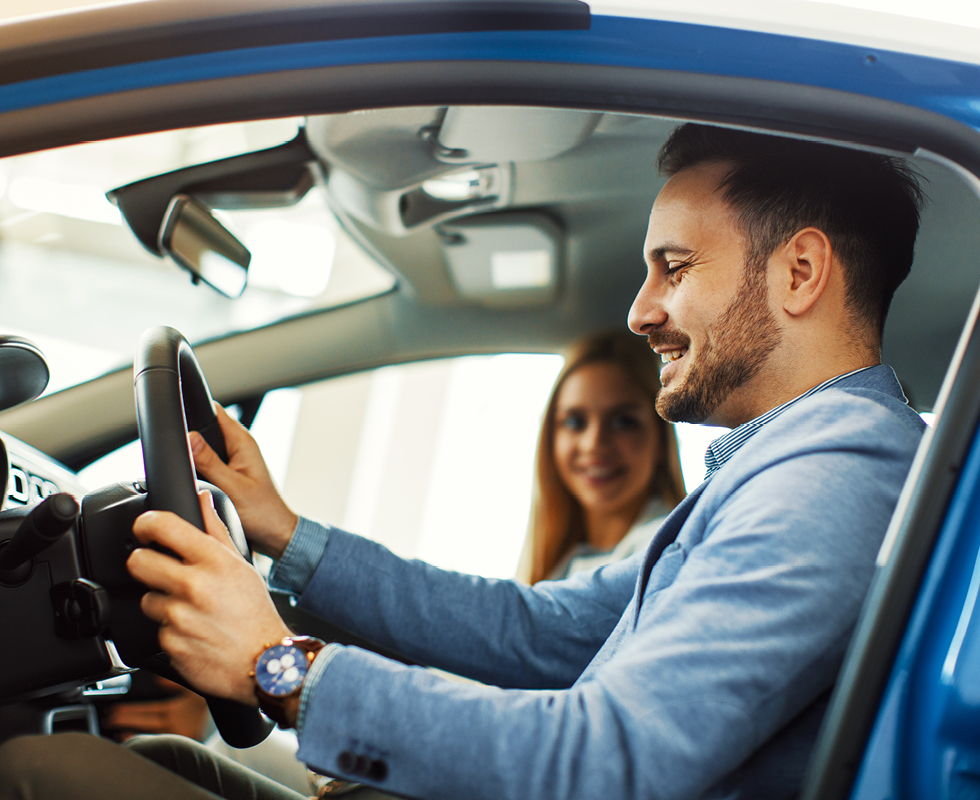 a man test drives a new car with a sales woman bought thanks to sdccu easy auto buying service