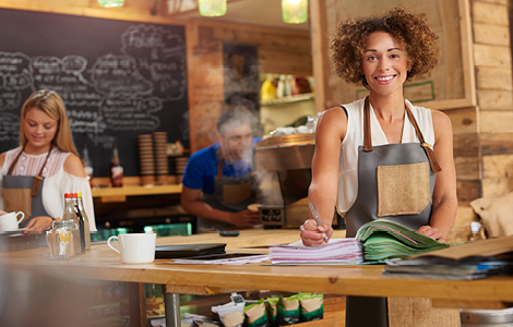 woman business owner working in cafe thanks to her SDCCU small business checking account