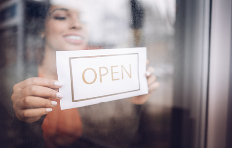 woman posting open sign on her new storefront thanks to sdccu commercial real estate loan
