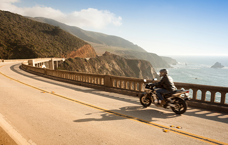 man on a motorcycle bought with sdccu motorcycle loan riding along the ocean coastline